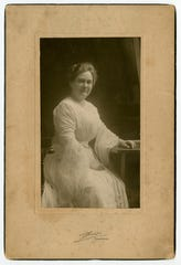 """Front caption (engraved on picture matting), """"Thuss, Nashville."""" Back caption (handwritten in ink), """"Return to Virginia Pearl Moore, Gallatin, Tennessee."""" A portrait photograph of Virginia P. Moore as a young woman with a sitting post."""