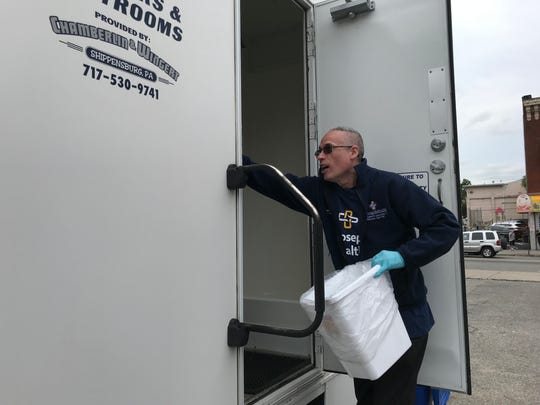 Joseph DeJesus, an employee of St. Joseph's health, emptying the trash at one of the mobile shower units.