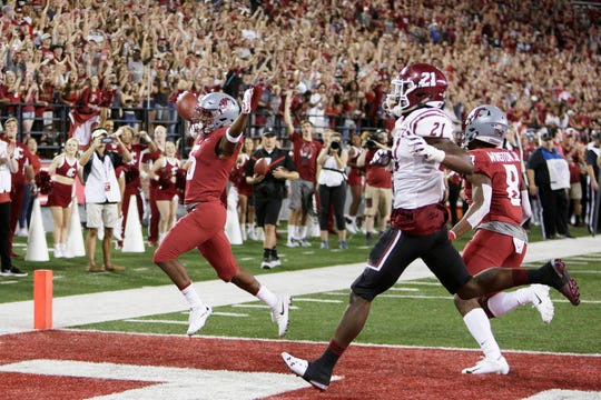 Washington State wide receiver Travell Harris, left, runs for a touchdown in front of teammate Easop Winston Jr., right, and New Mexico State defensive back Rodney McGraw II during the second half of an NCAA college football game in Pullman, Wash., Saturday, Aug. 31, 2019. Washington State won 58-7.