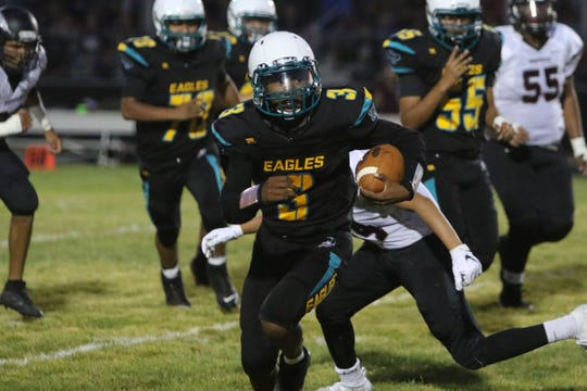 Navajo Prep's Dontrelle Denetso breaks free up the middle for a 20-yard run against Shiprock during Thursday's football game at Eagle Stadium in Farmington.