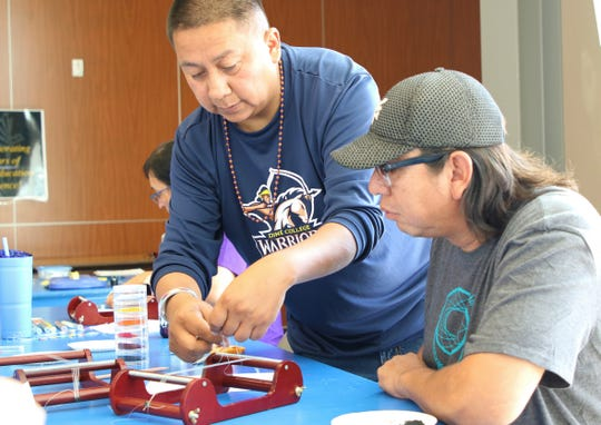 Instructor Dawayne Bahe, left, shows Allen Sandoval how to string a loom during the beading workshop by Navajo Cultural Arts Program on Sept. 6 at Diné College's south campus in Shiprock.