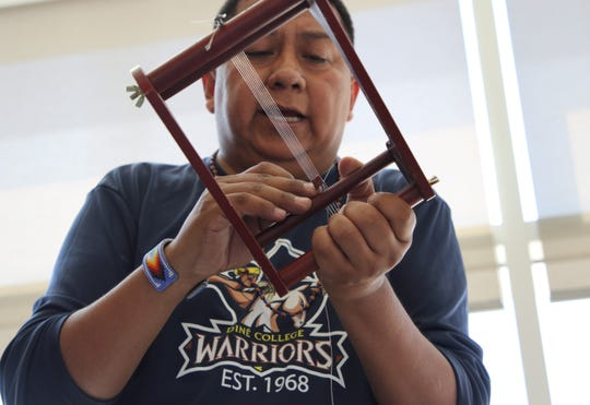Instructor Dawayne Bahe adjusts beads on a loom during a workshop sponsored by the Navajo Cultural Arts Program on Sept. 6 at Diné College's south campus in Shiprock.