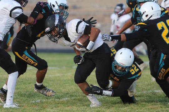 Navajo Prep's Adriano Begay (52) trips up Shiprock's Tye Harrison during Thursday's football game at Eagle Stadium in Farmington.