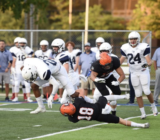 Brother Rice safety Gianni Dalimonte tackles Holy Names No. 22 Cyrus McGarrell in a game on Sept. 5.