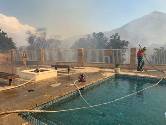 Two Wildfire Defense Systems firefighters, privately contracted firefighters hired by the United Services Automobile Association, battle flames threatening an insured home in the Copper Canyon neighborhood of Murrieta on Sep. 5, 2019.