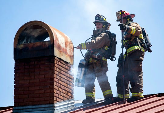 Navarre Beach Fire Rescue firefighters Rachel Provoznik and Shaun Hall make quick work of a chimney fire at the East River Smokehouse on Navarre Parkway on Friday. Voters will decide next month whether or not to create a special fire district so Navarre Beach firefighters can receive state retirement benefits.