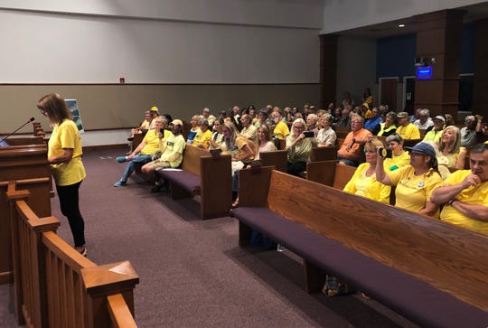Save Pensacola Beach founder Dianne Krummel speaks to the Escambia County Commission as members of the group in yellow shirts watch on Thursday, Sept. 5, 2019.
