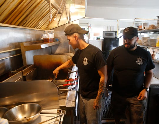 Café Con Leche owner Phil Cordero checks in on chef Daniel Velez at the cafe in New Hamburg on September 6, 2019.