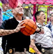 York County District Attorney's Office Detective Paul Pelaia takes a shot while Detective Scott James reacts to his while testing a basketball shooting game at the York Fair Friday, Sept. 6, 2019. Each year detectives for the DA's office walk the fair with game managers and play all the attractions to verify their fairness. Bill Kalina photo