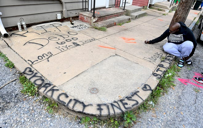 Najah Weedon of York City adds a memorial on the sidewalk near where a fatal shooting occurred on North Pine Street Friday, Sept. 6, 2019. She said she was a best friend of the victim. Bill Kalina photo