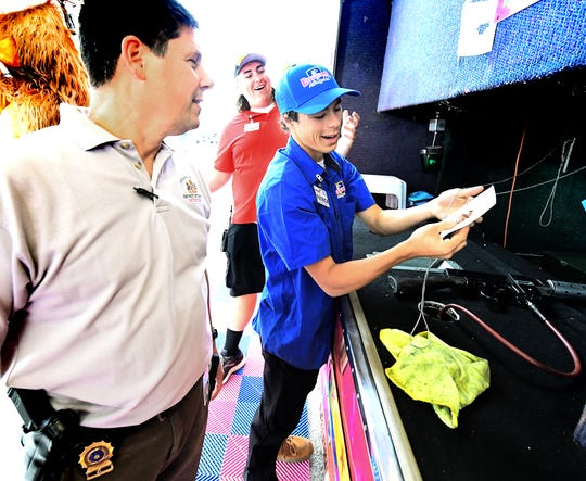 """Shoot the Star"" operator Patrick Dineen shows how he successfully obliterated the target to York County District Attorney's Office Detective Scott James at the York Fair Friday, Sept. 6, 2019. Deggeller Attractions concessions worker Dale Negus, Jr. reacts in the background. Each year detectives for the DA's office walk the fair with game managers and play all the attractions to verify their fairness. Bill Kalina photo"