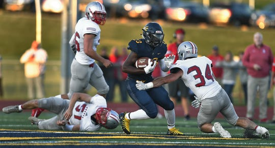 Victor's Rushawn Baker, center, tries to avoid a tackle by Canandaigua's Seth Vigneri during the season opener and the Teddi Bowl IV game at Victor High School, Thursday, Sept. 5, 2019. Proceeds from Teddi Bowl IV benefit Camp Good Days. Victor beat Canandaigua 31-14.