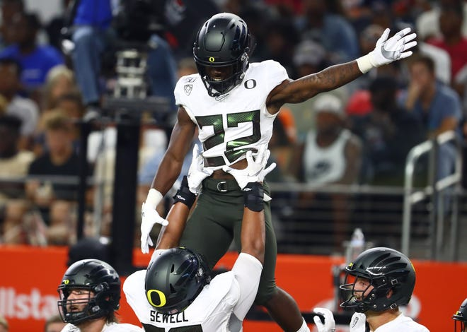 Aug 31, 2019; Arlington, TX, USA; Oregon Ducks running back Darrian Felix (22) celebrates a third quarter touchdown with tackle Penei Sewell (22) against the Auburn Tigers at AT&T Stadium. Mandatory Credit: Matthew Emmons-USA TODAY Sports