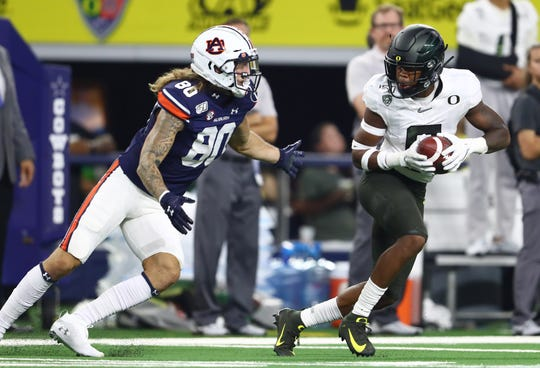 Aug 31, 2019; Arlington, TX, USA; Oregon Ducks safety Jevon Holland (8) intercepts the ball in the second quarter against Auburn Tigers receiver Sal Cannella (80) at AT&T Stadium. Mandatory Credit: Matthew Emmons-USA TODAY Sports