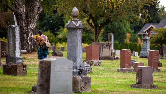 A visitor brings flowers to the City View Cemetery in Salem, Oregon, September 5, 2019.