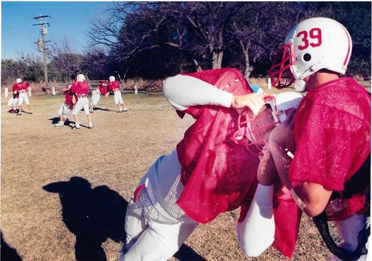 Christoval High School's Oscar Duke (39) helps Jon Fred McNeil with warm-up drills during during practice Tuesday, Dec. 11, 1990, in Christoval in preparation for the six-man state championship game on Dec. 15, 1990.