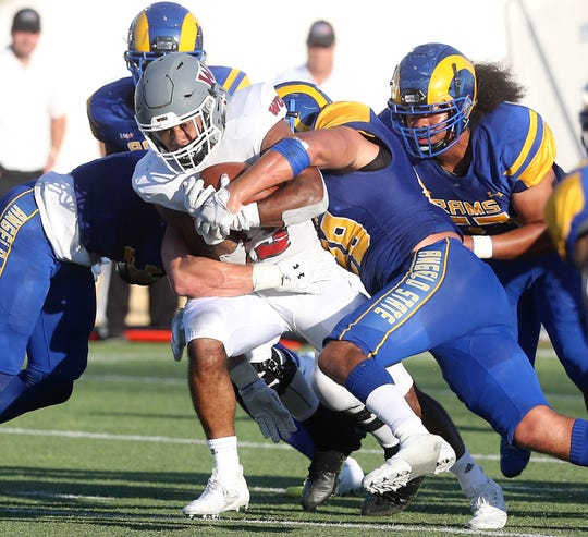 A Western Oregon player gets bottled up by the Angelo State University defense during the season opener at LeGrand Stadium at 1st Community Credit Union Field Thursday, Sept. 5, 2019.