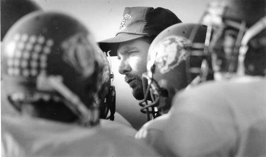 Head coach Billy Barnett talks to a player during a huddle with his team from Dell City in 1993.