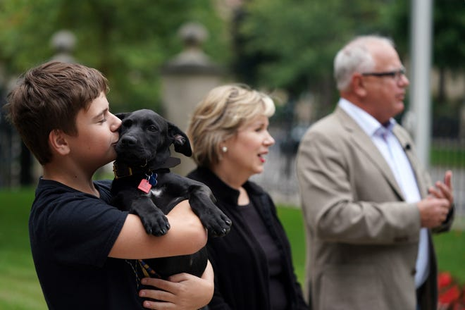 Gus Walz, left, holds Scout, a 3-month-old Labrador Retriever the Walz family adopted, during a news conference to announce the family's newest addition at the governor's residence Thursday, Sept. 5, 2019. First lady Gwen Walz, center, and Gov. Tim Walz, right, look on. (Anthony Souffle/Star Tribune via AP)