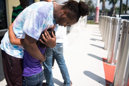 AJ Reckley, of West Palm Beach, hugs his cousin, Angel Reckley, 6, outside U.S. Customs and Border Protection at Witham Field on Friday, Sept. 6, 2019, in Martin County. Angel had recently arrived after evacuating the Bahamas following Hurricane Dorian's devastation of Marsh Harbour on the Abaco Islands.