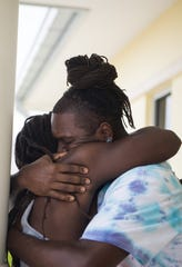 "AJ Reckley (right), of West Palm Beach, shares a long embrace with brother Rashad Reckley, who evacuated Marsh Harbour on the Abaco Islands of the Bahamas, outside U.S. Customs and Border Protection at Witham Field on Friday, Sept. 6, 2019, in Martin County. Rashad Reckley's fiancee, T'Quylla Thompson, said that during Hurricane Dorian, ""the water was all the way to the ceiling, we had to swim out the house — literally hanging on from the tree until the eye of the storm came and water came down about chest deep."" Her fiance added, ""that's when we had the opportunity to go the hotel ... and wait out the rest of the storm until it was done."""