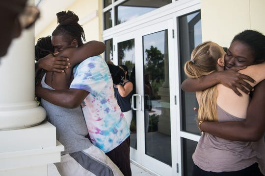 "AJ Reckley (second from left), of West Palm Beach, shares a long embrace with brother Rashad Reckley, who evacuated Marsh Harbour in the Abaco Islands of the Bahamas, outside U.S. Customs and Border Protection at Witham Field on Friday, Sept. 6, 2019, in Martin County. Rashad Reckley's fiancee, T'Quylla Thompson (far right), hugs Tara Hauck, also of West Palm Beach. Thompson said that during Hurricane Dorian, ""the water was all the way to the ceiling, we had to swim out the house — literally hanging on from the tree until the eye of the storm came and water came down about chest deep."" Her fiance added, ""that's when we had the opportunity to go the hotel ... and wait out the rest of the storm until it was done."""