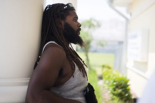 Rashad Reckley waits for family outside U.S. Customs and Border Protection at Witham Field on Friday, Sept. 6, 2019, in Martin County. He had evacuated with fiancee T'Quylla Thompson after surviving Hurricane Dorian's destruction of Marsh Harbour in the Abaco Islands of the Bahamas.