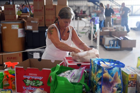 "Camille Geib, of Port St. Lucie, sorts through and packs donated items for Hurricane Dorian relief to the Bahamas from the public on Friday, Sept. 6, 2019 in the main hangar of Missionary Flights International at the Treasure Coast International Airport and Business Park in Fort Pierce. ""I found out about the volunteer work through my church,"" Geib said, ""and so I'm here to help out in any way I can."" Donations of personal hygiene products, tarps, food and children and baby items are still needed."