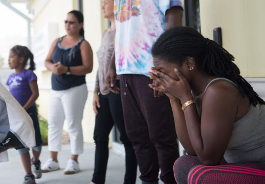 "T'Quylla Thompson, who had evacuated with fiance Rashad Reckley from Marsh Harbour on the Abaco Islands of the Bahamas, unites with Reckley's family from West Palm Beach outside U.S. Customs and Border Protection at Witham Field on Friday, Sept. 6, 2019, in Martin County. Thompson said that during Hurricane Dorian, ""the water was all the way to the ceiling, we had to swim out the house — literally hanging on from the tree until the eye of the storm came and water came down about chest deep."""