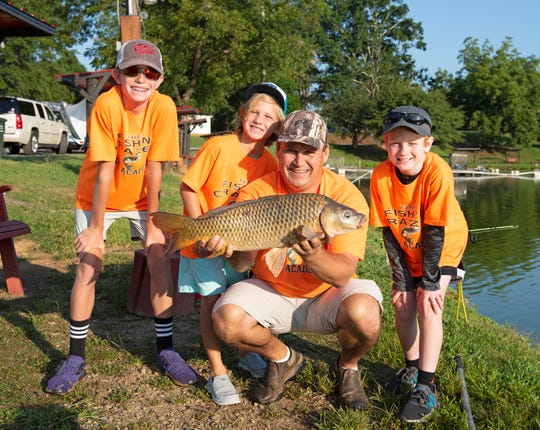 Xavier Tiberghien holds a fish that was caught during the Fishin' Crazee Kids Academy at Cannon's Fishing Lake in Greer.