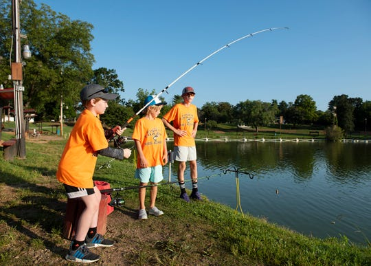 Brayden Stack, 10, reels in a fish while fishing with Carson Allison, 9, middle, and Tucker Jones, 13, at Cannon's Fishing Lake in Greer as part of the Fishin' Crazee Kids Academy.