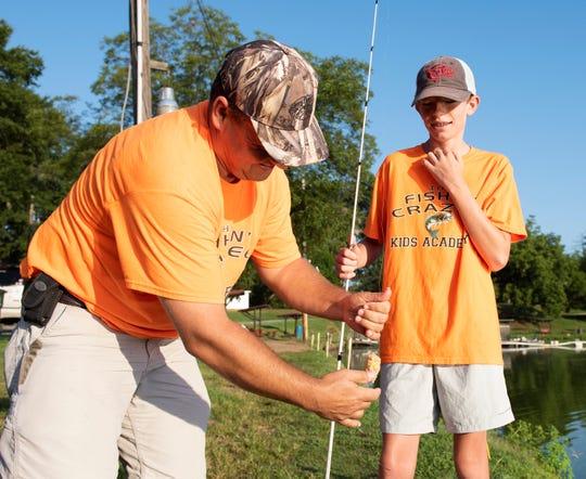 Xavier Tiberghien helps Tucker Jones bait a hook during Fishin' Crazee Kids Academy at Cannon's Fishing Lake in Greer.