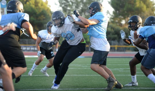 Ivory Jackson, defense end for Moorpark College,  pushes and drives in at practices. The team will play Saturday evening.