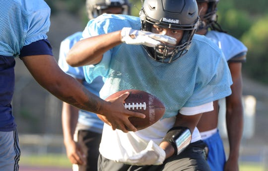 Edyon Batta takes handoff during the Moorpark College football team's practice on Thursday. Batta, a sophomore, is part of a deep group of running backs.