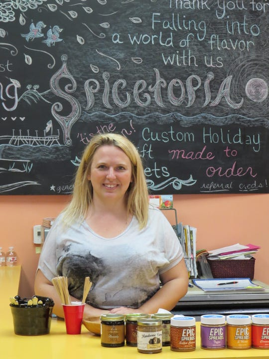 SpiceTopia owner Ashley Pope poses behind the tasting counter at the Ventura shop, which sells several lines of locally made food items.