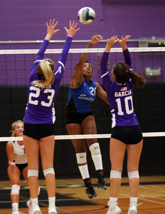 Hen Hud's Amya Davis (20) gets a shot by John Jay's Lily Preis (23) and Bella Garcia (10) during volleyball action at John Jay High School in Cross River Sept. 5, 2019.