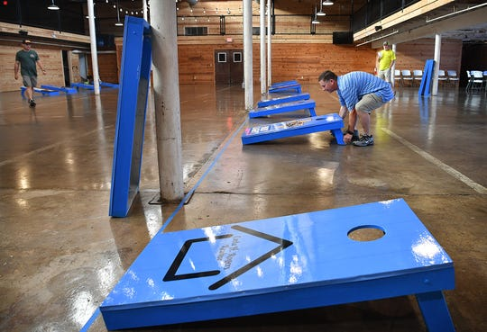 Louis Garrett of Leadership Wichita Falls helps set up boards for the Bags for Brags Cornhole Tournament at The Warehouse Friday morning.