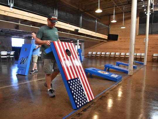 Leadership Wichita Falls member Rusty Downs sets up one of 12 lanes of play for the Bags for Brags Cornhole Tournament at The Warehouse. One hundred teams are signed up for the double elimination event that raises money for LWF and the Childrens Aid Society.