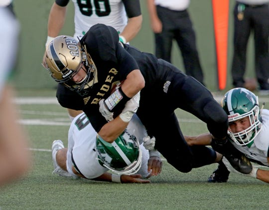Rider's Ranse Radtke is tackled by Azle defenders Thursday, Sept. 5, 2019, at Memorial Stadium.