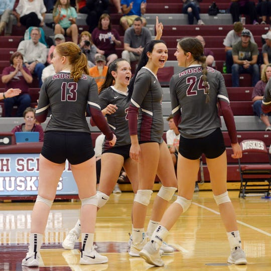John Glenn players celebrate after clinching a 25-15, 25-20, 11-25, 20-25, 15-9 win against visiting Maysville on Thursday night in New Concord.
