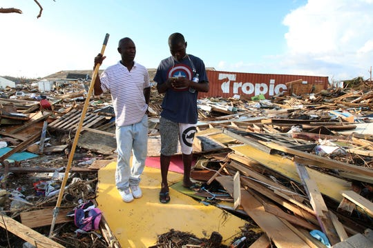 Haitian Burris Filburt, right, and another man stand on the extensive damage and destruction in the aftermath of Hurricane Dorian is seen in The Mudd, Great Abaco, Bahamas, Thursday, Sept. 5, 2019. The Mudd was built by thousands of Haitian migrants over decades. It was razed in a matter of hours by Dorian, which reduced it to piles of splintered plywood and two-by-fours 4 and 5 feet deep, spread over an area equal to several football fields.