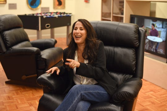 "Maggie Wheeler, who played Janice on ""Friends,"" sits in a recreation of Joey and Chandler's apartment at a pop-up exhibit in New York."