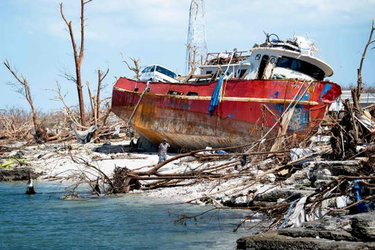 People recover items from a beached boat after Hurricane Dorian on September 5, 2019, in Marsh Harbor, Great Abaco.
