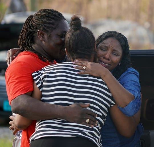 Nassau resident Sandra Ferguson, 55, right, embraces her brother, Dereck Bain, 46, and their sister Judy Rolle, 51, in Marsh Harbour on Abaco in the Bahamas after a nerve-wracking trip to the disaster left behind by Hurricane Dorian. Ferguson and Rolle couldn't reach their brother via cell phone and flew to the island in hopes they could find him.