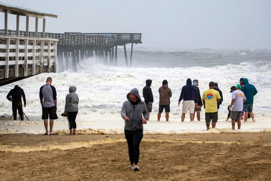 People gather to watch the waves during Hurricane Dorian at the Virginia Beach Fishing Pier.