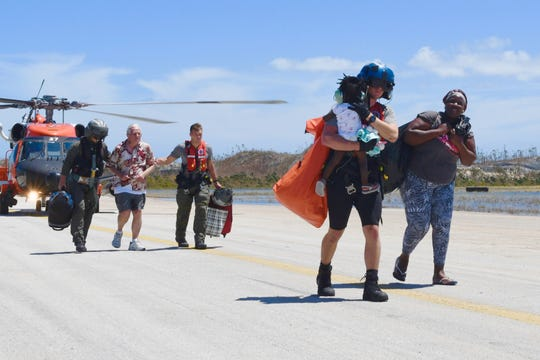 A USCG Air Station Clearwater helicopter crew evacuates Hurricane Dorian displaced adults and children to safety, in Marsh Harbour, Bahamas, on September 5, 2019.