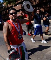 Julio Silvas waves to the crowd while marching with the Team Flores Abilene Fight Club float during Saturday's West Texas Fair & Rodeo Parade.