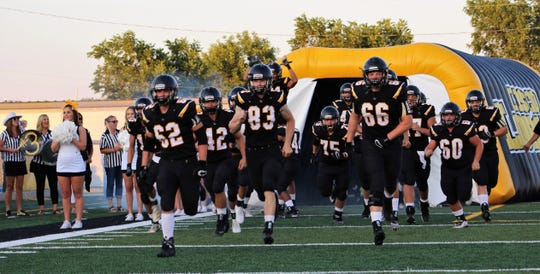Led by Koby Cordero (62), Kolten Sutton (83) and Caden Burleson, the Cisco Loboes run onto the field for Friday's game against Wall. The Hawks won, 20-13, but Sutton had a first-half interception. Sept. 6 2019