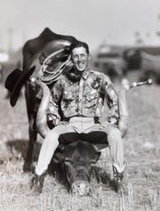 An undated photograph from the 1930s or 40s of Monte Reger sitting between the horns of Bob-Cat Twister, a longhorn he trained to leap over automobiles.