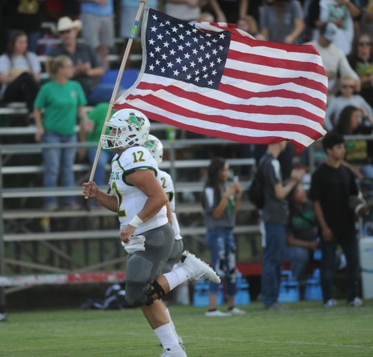Dublin senior quarterback Cy Wing runs with the U.S. flag before a game against Albany on Friday, Sept. 7, 2019, at Robert Nail Memorial Stadium in Albany.